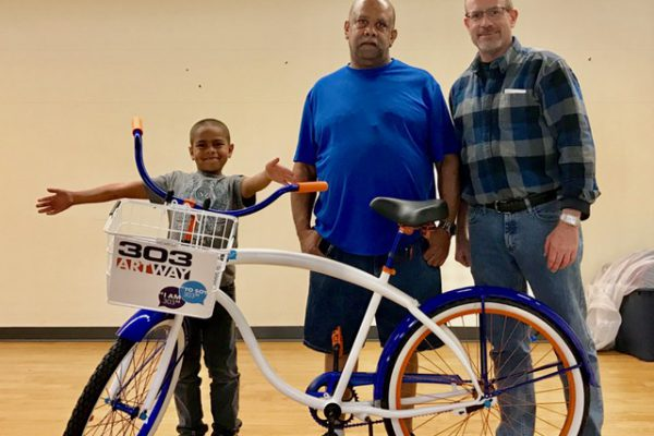 Eric Johnson (center) was the proud winner of a bike at 303 ArtWay's premier bike giveaway event. Will Kralovec, ULC's Director of Master Site Development, celebrated his win.