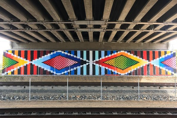 A mural beneath the 40th and Colorado Commuter Rail Station on RTD's A line. The mural was created by Birdseed Collective, a nonprofit artistic organization dedicated to community improvement. James Jewkes currently sits on the Board of Birdseed Collective.